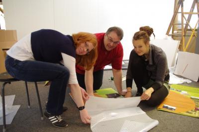 Anni Fay (r. i. Bild) mit Ihren Helfern Nele Voss und Andreas Ahne beim Kleben der Bildtafeln